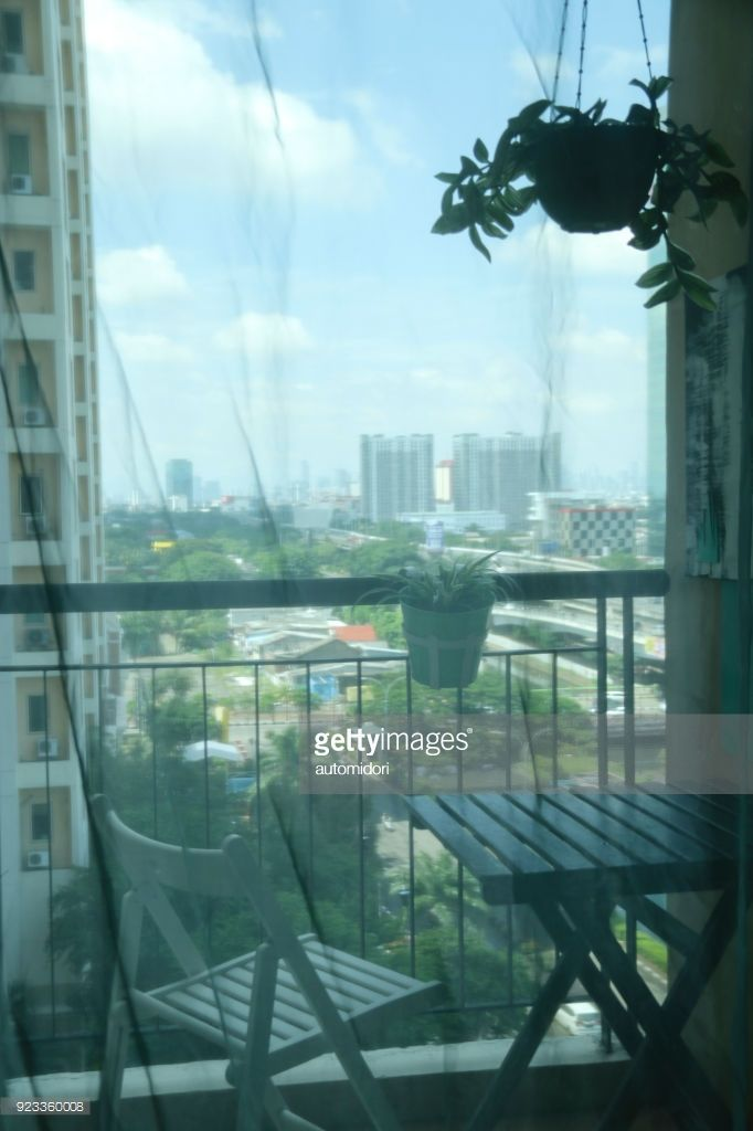 A view to the balcony from inside an apartment unit. From the balcony is a glimpse of Jakarta (Indonesia) aerial view in the morning. The furniture are made of sustainable material (resource) and recyclable.