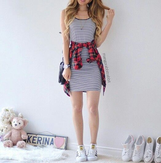 A spaghetti strap black and white striped t-shirt dress paired with Adidas Superstar sneakers, and a red flannel.