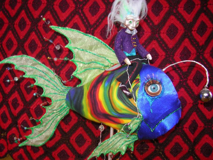 """Hi, this is a design I did a couple of years ago, I call it """"Fish Master"""" I got the eyes out of one of those big hair do dolls from the sallies,I think it kind of makes the fish look enchanted, sad though, there are definately elements of slavery here.I always thought it would be great as a night light but have only just managed to do it. #clothdoll #clothfish #artdoll"""