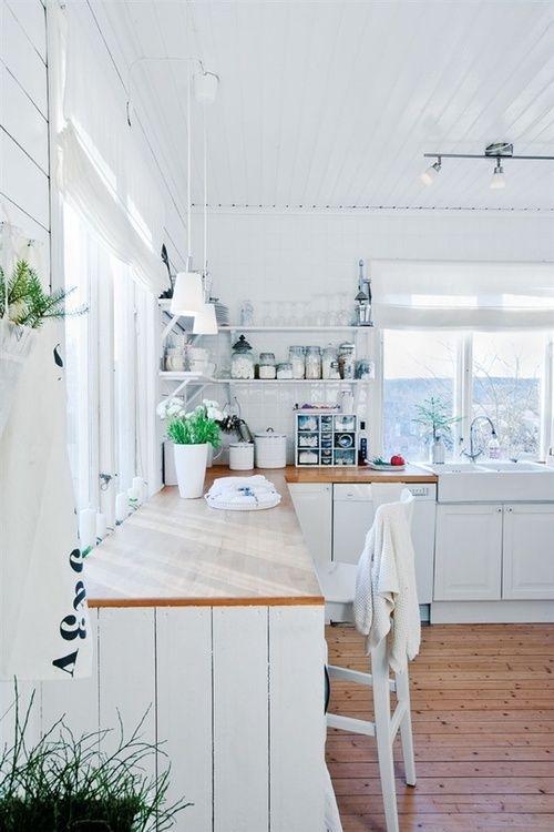 Beaucoup de blanc, des comptoirs en bois, et une touche de vert.