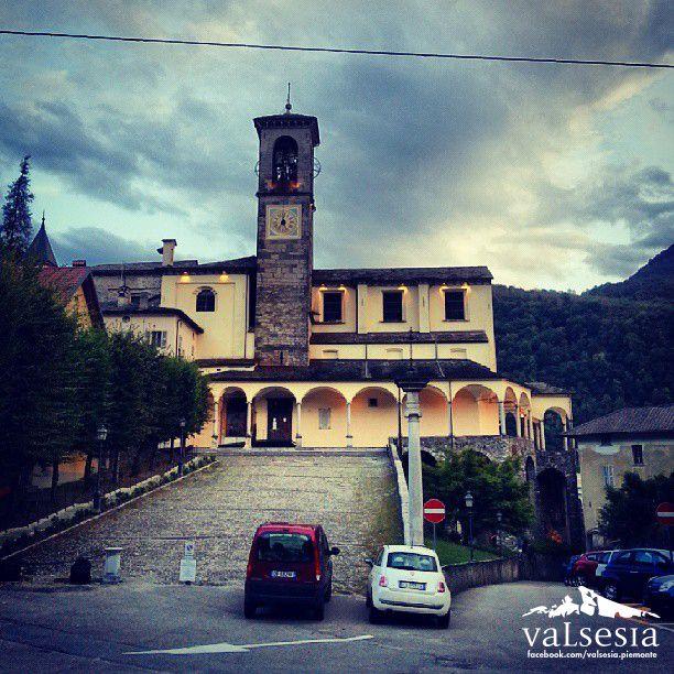 Si fa sera sulla Collegiata di San Gaudenzio.  La chiesa principale dell'abitato di Varallo, costruita su di un piccolo promontorio roccioso al centro della cittadina, domina dall'alto la piazza Vittorio Emanuele.