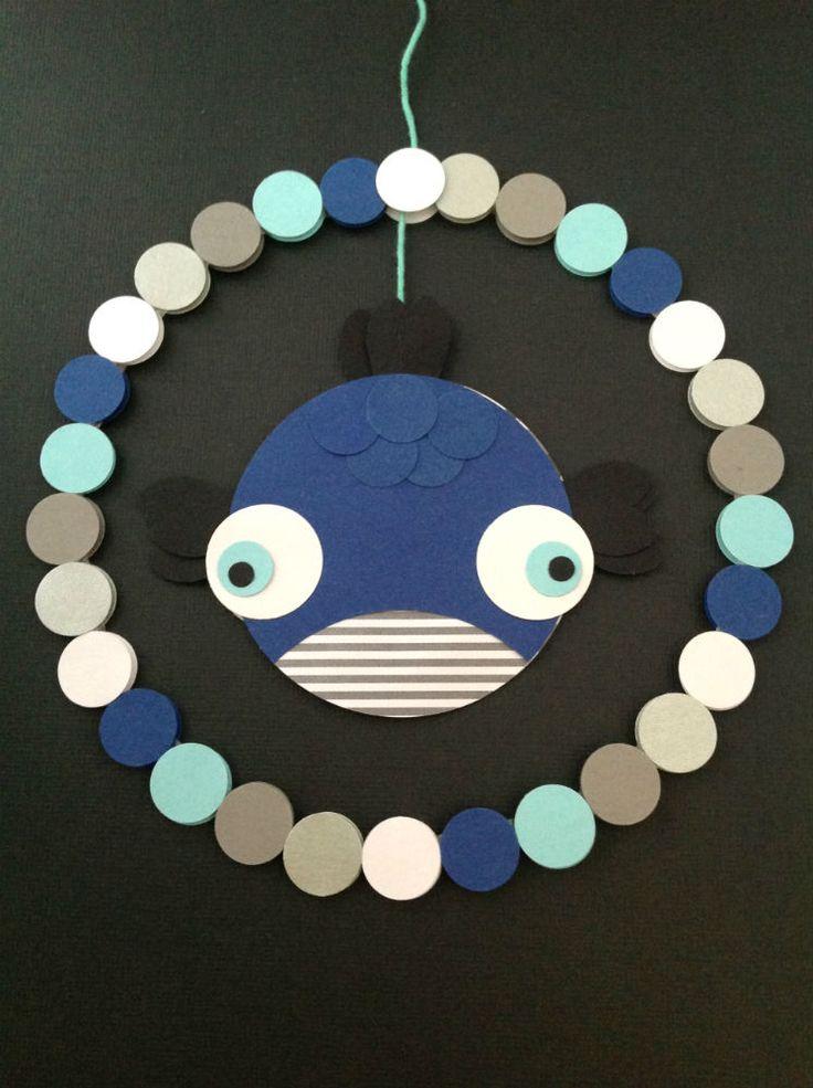 FISKEURO I MARITIME FARVER Blå fisk i en cirkel af prikker i blå, grå, hvid, lys turkis og perlemorssølv. www.jannielehmann.dk