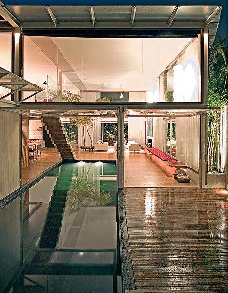 No projeto do escritório Bernardes Jacobsen, a piscina invade a sala, formando dois corredores nas laterais. Um leva à suíte e, o outro, ao quintal com deque. A escada é solta em cima para não ter paredes dividindo os ambientes.