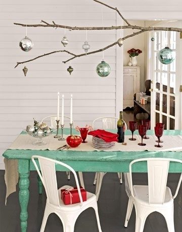 branch with baubles suspended, and deliciously blue/turquoise painted table, white chairs (love) and simple setting.