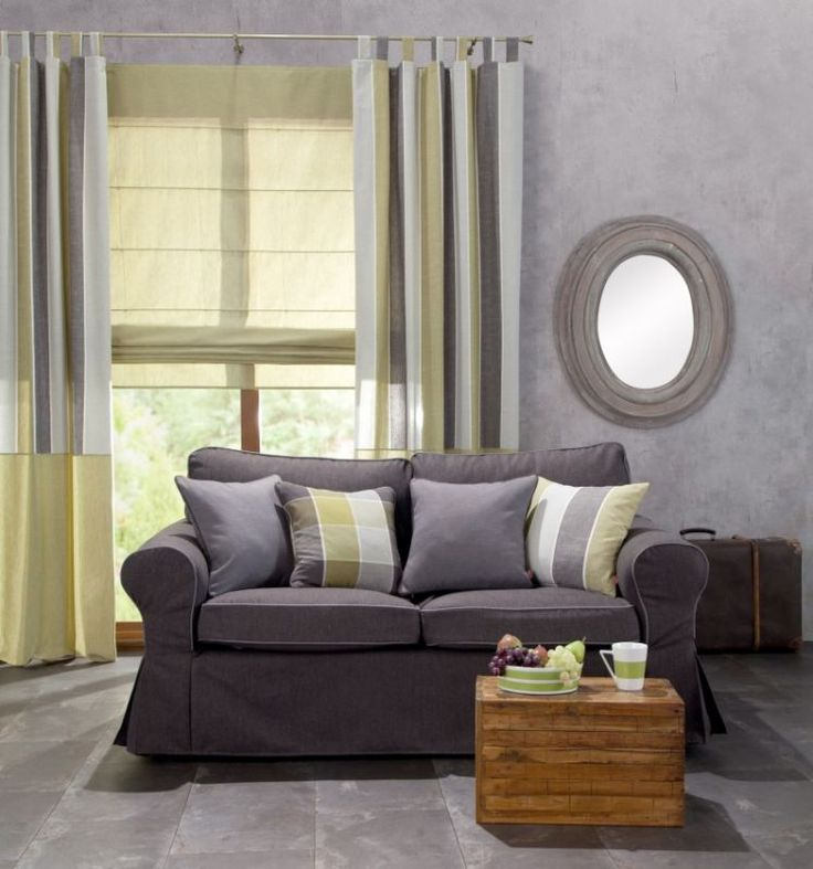Varicolored, patterned pillows combined with a gray couch.