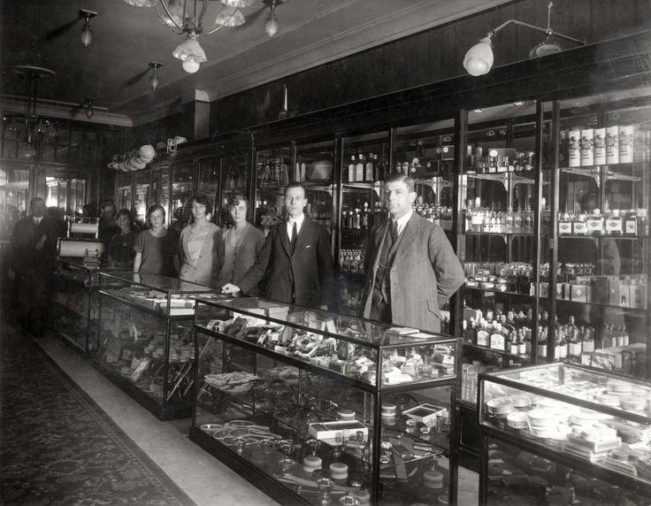 Interieur van parfumerie Apollo in Den Haag, met bij de toonbanken en vitrinekasten een rij verkopers en verkoopsters. Nederland, 1924.
