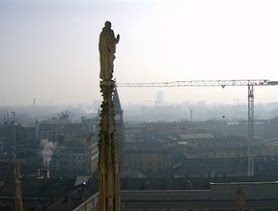 A Saint looks over Milan from the top of the cathedral.