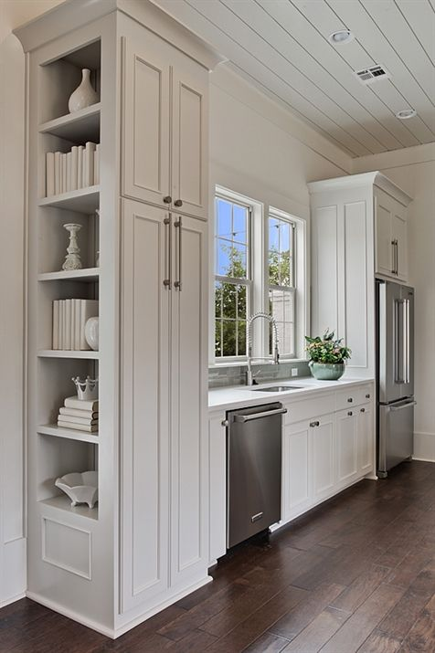Small, efficient kitchen features a gray paneled ceiling dotted with pot lights over gray cabinets accented with raised panel doors paired with white quartz counters framing a stainless steel sink and pull out faucet as well as a gray stone backsplash with a stainless steel dishwasher to the left and an under cabinet refrigerator to the right.