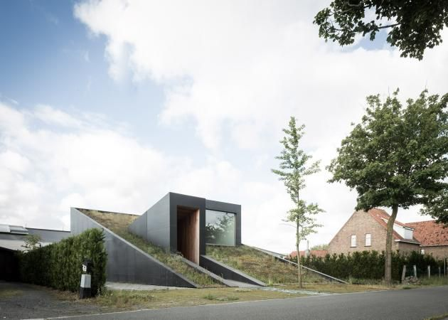 An angular entrance and roof intersect the plant covered roof of this wedge shaped house completed by architects office oyo in belgian village maldegem
