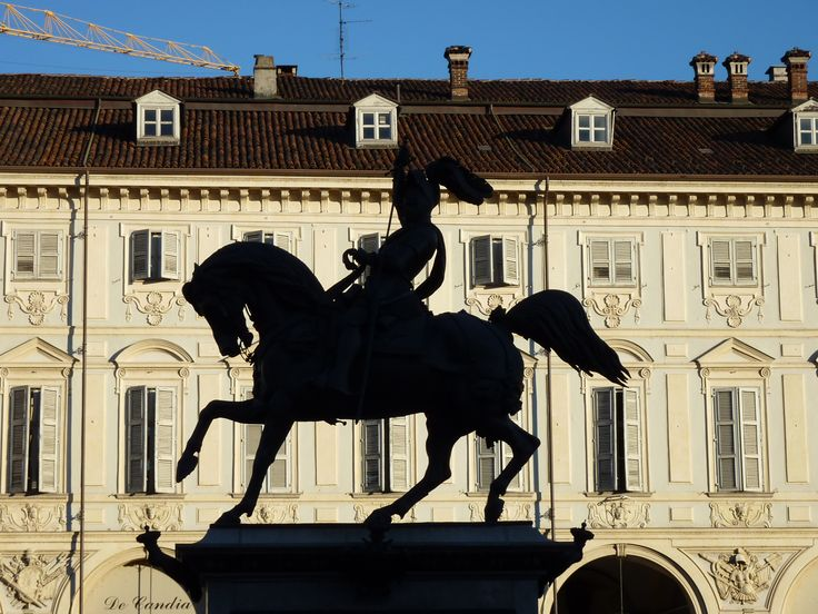 """Sagome di bronzo: il """"caval 'd brôns"""", il monumento equestre del principe sabaudo Emanuele Filiberto, che nel 1563 spostò la capitale del ducato da Chambéry a Torino, conosciuto dai torinesi come il caval 'd brôns, è collocato al centro di Piazza San Carlo. In questa foto di un pomeriggio di sole, il monumento si staglia come una sagoma sulla facciata dei Palazzi di Piazza San Carlo."""