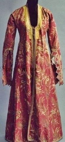 Turkish caftan. Late-Ottoman, c. 1900.  Woman's open coat (robe) of dark red silk embroidered overall with couched gold thread in leaf and floral pattern, scoop neck with buttons at bust, trimmed with gold braid, as are pocket slits, long sleeves open and zig-zag to elbow, trimmed with gold braid. Lined with pink cotton with red and green leaf pattern in stripes. (Kent State University Museum).