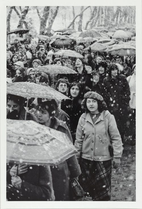 During the Iranian Revolution, women protest Ayatollah Ruhollah Khomeini's decree requiring all women to wear a veil in public .