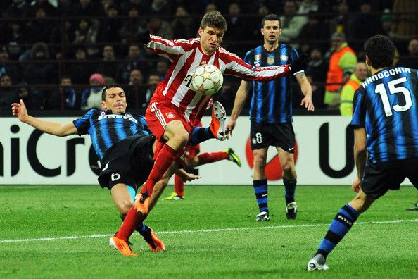 Lucio of Inter Milan tussles for posession with Thomas Muller of FC Bayern Muenchen during the UEFA Champions League round of 16 first leg match between Inter Milan v FC Bayern Muenchen on February 23, 2011 in Milan, Italy.