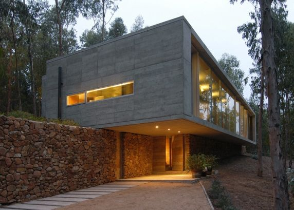 """House by Gubbins Arquitectos: """"..Chilean architect Pedro Gubbins designed this concrete residence as a rural retreat for himself and his family and has balanced it on top of a dry-stone wall.."""