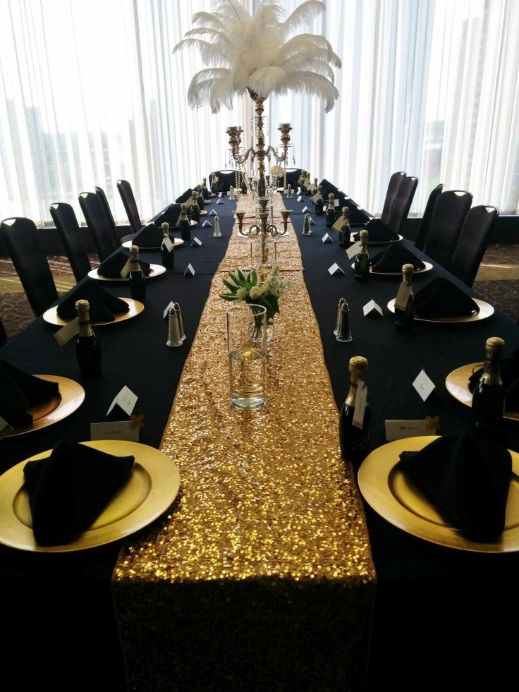 Black Table Linens, Gold Charger Plates, Black Napkins (pyramid fold), Gold Sequin Runner, Small Floral in vase, Large Gold Candelabra with Peacock Feathers, Pearl Garland, Tea Lights and Round Mirror – Millennium Hotel