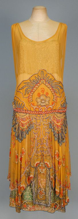 BEADED CHIFFON DINNER DRESS with METALLIC LACE, 1920s. Sleeveless pumpkin silk decorated with elaborate polychrome beadwork and pearls, scalloped and lobed front hem with back streamers revealing satin under-dress with beaded and metallic lace hem and lace bodice top. Front