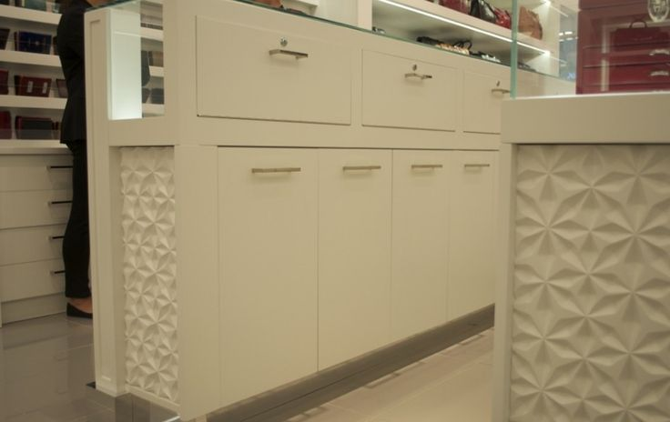 Textured panels in a white monochromatic location give just the right amount of vivacity to the site, without stealing the stage from the products at this retail location.