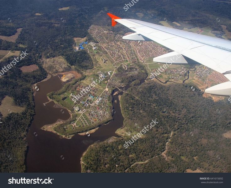 airplane wing and Earth view with river, lake and houses.