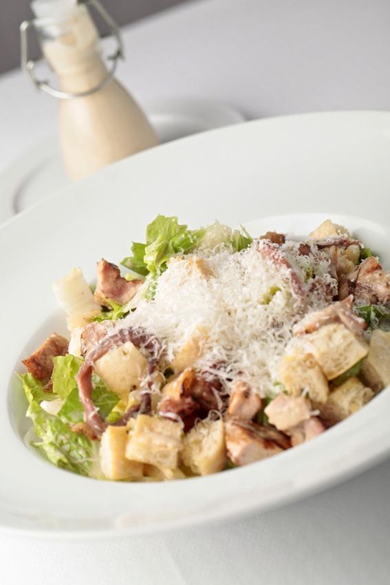 Ensalada César Cardini, Lechuga romana, costrones de pan al orégano y pollo a la parrilla. Acompañada de la original salsa César: aceite de oliva, queso parmesano y anchoas.