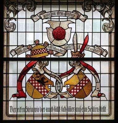 Fensterwand zur Geschichte des Märkischen Sauerlands. - Unter dem Rosenwappen der Grafen von Altena und Isenburg sind die Grafen Adolf I. von Altena und Mark und Engelbert III. von der Mark im Wappen vereint. Fa. Linnemann, 1909. Fenster im Ständesaal, Landratsamt Altena.