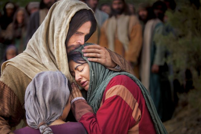 Mary and Martha embrace Jesus Christ as He stands and comforts them in His arms.