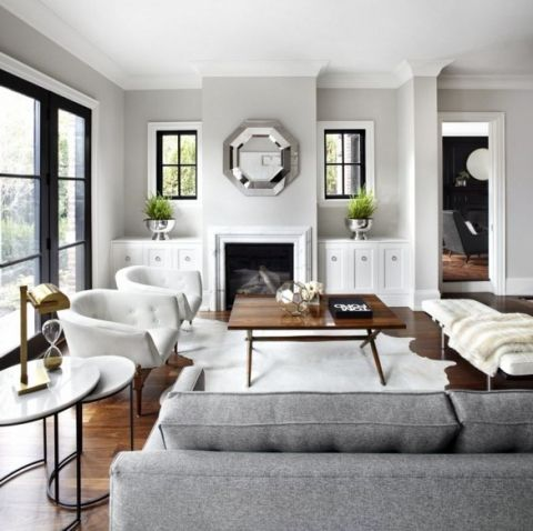 This space has a much more sophisticated feel to it. Black window trim adds contrast against the light grey walls. Neutral living room.
