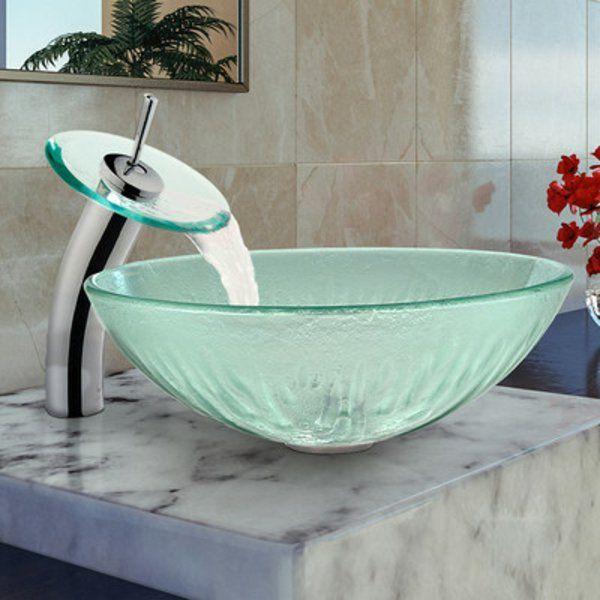 robinet cascade et évier en verre sur un comptoir en marbre