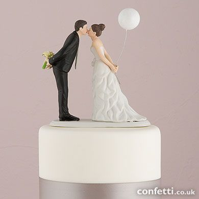 Leaning in for a Kiss – Balloon Wedding Cake Topper. This couple is sweetly leaning forward for a kiss as husband and wife! Wearing a beautiful bowed dress and clasping a balloon, this beautiful bride is leaning towards her one true love as he holds onto her bouquet. Great for a princess theme!