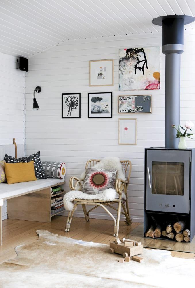 En enkel benk av sponplater strekker seg langs veggen, dekket av tynne, hvite puter for bedre sittekomfort. Ryggputene er festet på veggen ved hjelp av lærstropper. Den grå vedovnen står som en fint kontrast mot den hvite veggen.