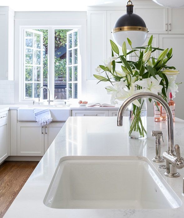 A+long+kitchen+island+is+fitted+with+a+white+porcelain+sink+lit+by+a+Hicks+Pendant.