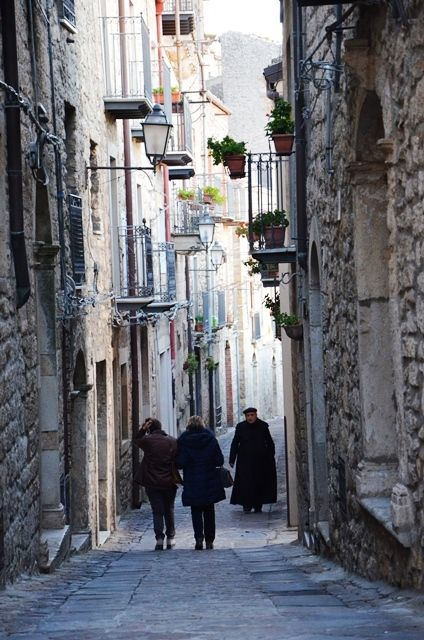 The typical narrow streets of a Sicilian village. Here we are in Gangi, on the Madonie Mounts and the priest is walking to the Church for a funeral.