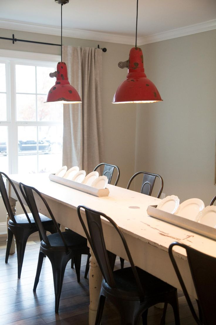 Vintage red pendant lights hang over the long farmhouse for Long dining table lighting
