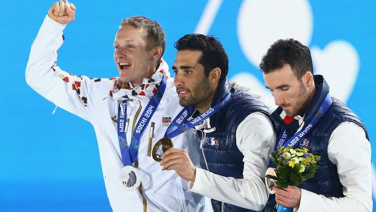 Silver medalist Ondrej Moravec of the Czech Republic , gold medalist Martin Fourcade of France and bronze medalist Jean Guillaume Beatrix, also of France, pose for a group shot upon receiving their respective medals for the Biathlon men's 12.5 km pursuit at the Medal Ceremony.