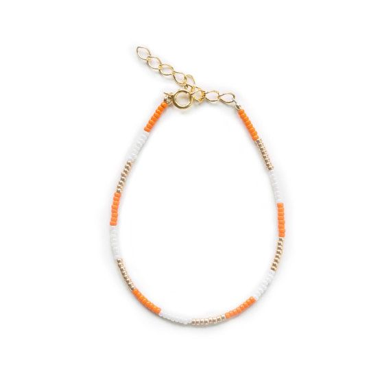 Dainty Beaded bracelet with gold, orange and white beads  Extender chain in Gold plated Sterling Silver. Length:  15-22 cm  Care instructions: Sterling silver tarnishes over time. In order to prevent tarnishing please use a polishing cloth. Please handle your jewelry with care and do not wear the jewelry whilst bathing. Avoid exposing you jewelry to creams and chemicals such as chlorine.Always store your jewelry in a dry room.