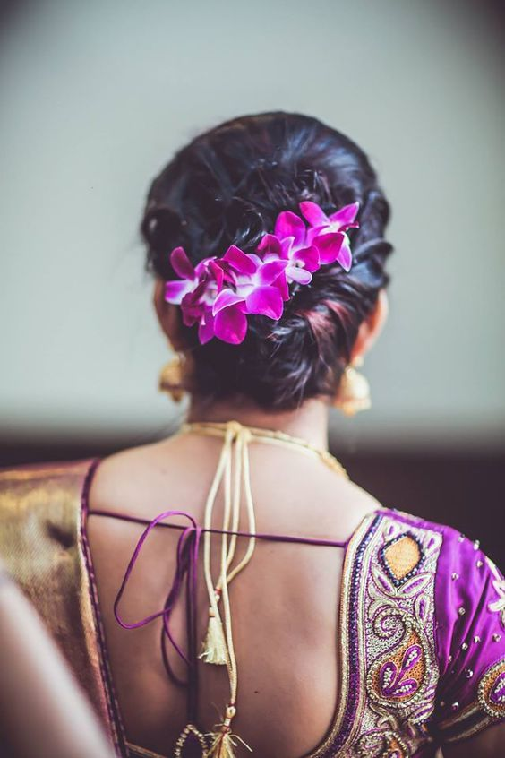 Curling up your hair pulling it in a stylish updo and adding a single string of flowers that matches your saree fulfils traditional nuances in a trendy fashion
