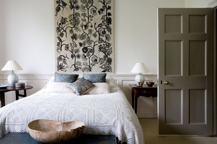 The easiest headboard solution we know of? A textile panel hung on the wall (either draped on a wall-mounted curtain rod or simply nailed to the wall).