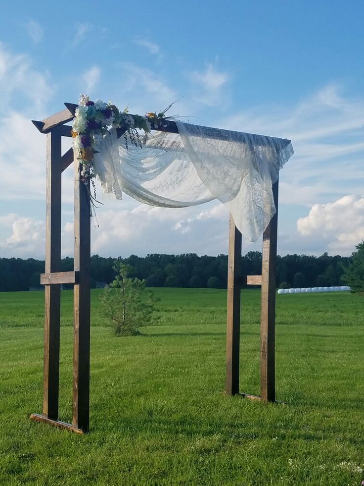 Homemade wedding arch for my sisters outdoor wedding! Guests sat on bails of hay for the ceremony! Cut from wood, stained, added flowers and a lace curtain! Beautiful!