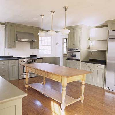 Farm kitchen with grey/green cabinets and furniture island