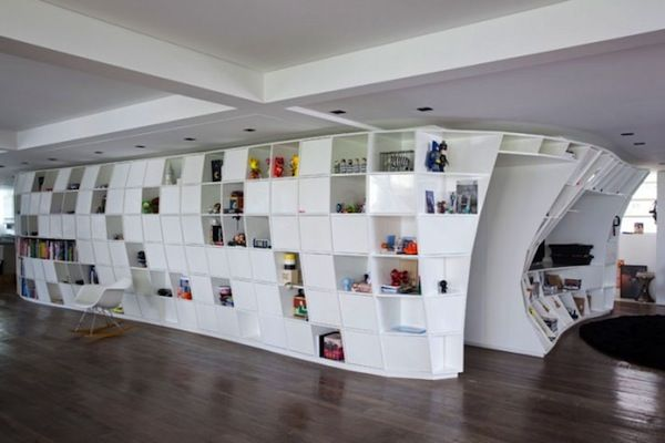 This contemporary pad in Brazil designed by Triptyque Studio features an incredible, large-scale, wraparound bookcase as the apartment's focal point.