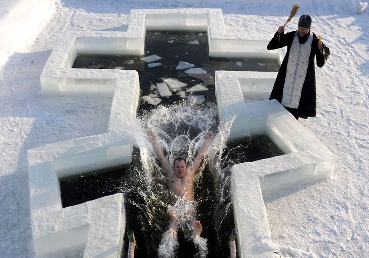 A Belarus Orthodox believer plunges into icy waters as a priest blesses him on the eve of the Epiphany holiday in Pilnitsa