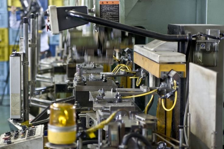 ステンレスの板が軽快に流れて行くプレス機のライン。