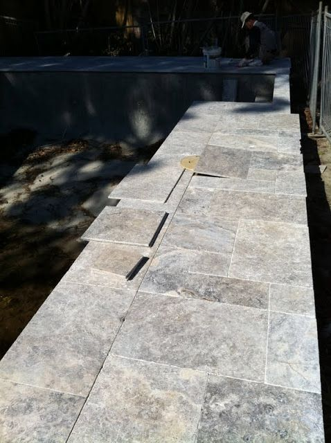 Silver Travertine paving around pool edge in a French Pattern.