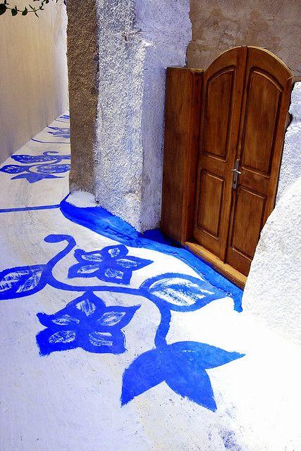 Narrow alleyway with blue flowers and wooden gate. Karterados village. Santorini island, Cyclades, Greece