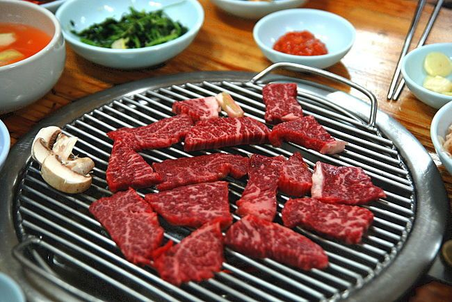 Typical charcoal Korean barbecue setup up where the hot coal are added to the unit set in a table at the restaurant. Learn how to do this at home