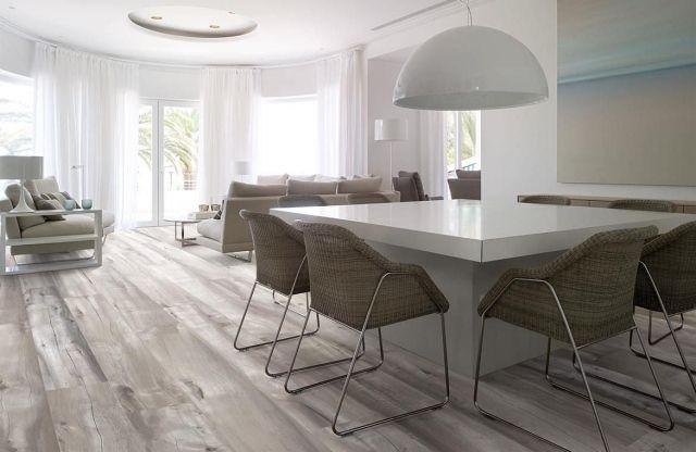 Carrelage imitation arquer vieilli avec plusieurs nuances pour recréer l'apparence du bois. Le mobilier contemporain place le salon dans une esthétique moderne