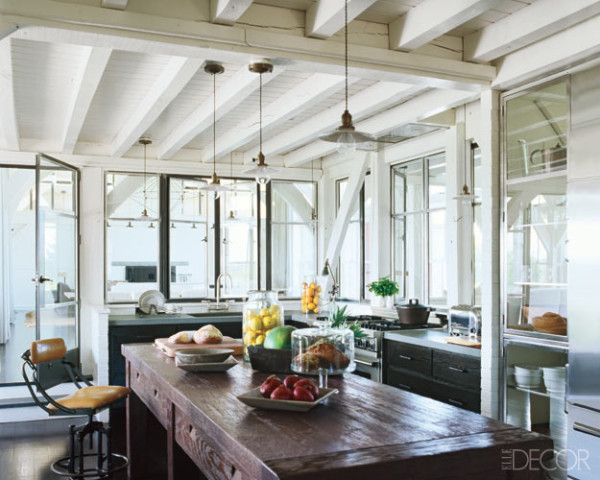 In the Martha's Vineyard beach house of actress Meg Ryan, pendant lights from Historical Materialism are installed above an oak table in the kitchen; the range is by Viking.