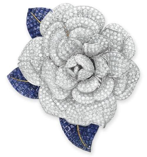 A DIAMOND AND SAPPHIRE FLOWER BROOCH Designed as a pave-set Diamond Camellia Blo...