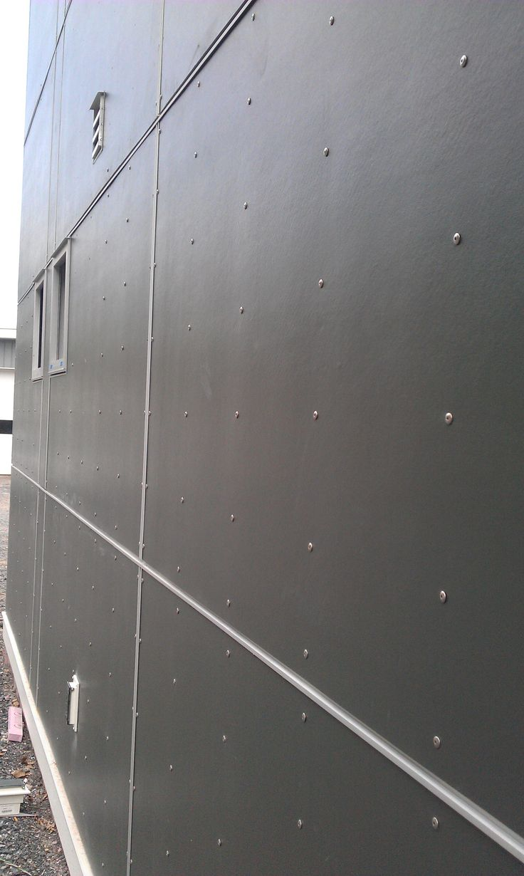 James Hardie panels in dark grey with exposed fastening screws to give a rivet look.