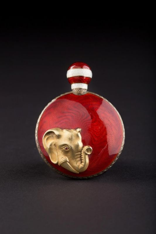 A FABERGÉ JEWELLED SILVER AND GUILLOCHÉ ENAMEL PILL BOX AND PERFUME FLASK. Workmaster Anna Ringe, St. Petersburg, 1908-1917. The surface of translucent red enamel over wavy sunburst engine-turning. The lid centred with a rose-cut diamond. The spherical cover with red and white enamelled bands. The reverse later set with a gold head of an elephant. Gilt interior.