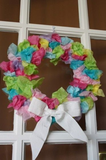 Easter wreath made with tissue paper hanging on a door.